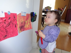 My 16-month old proudly looking at her Fridge Art