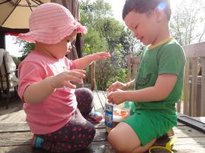 Caleb playing with his little sister Naomi (almost 1.5 years old) on the deck.