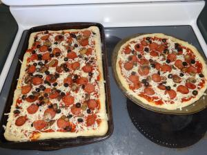 First layer of toppings (tomato paste or sauce, mozzarella cheese, black olive, pepperoni)