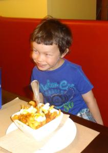 Caleb's first experience of poutine at Frite Alors! in downtown Montréal.